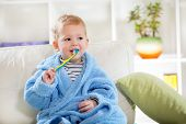 stock photo of teething baby  - Little baby boy with tooth brush in the living room - JPG