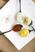 stock photo of condiment  - variety condiments on spoon put on white plate - JPG