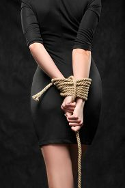 picture of slavery  - female hands tied behind his back with a rope - JPG