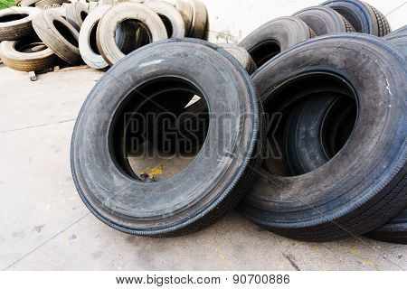 Tires Stacked Near Cement Wall, Used Tires