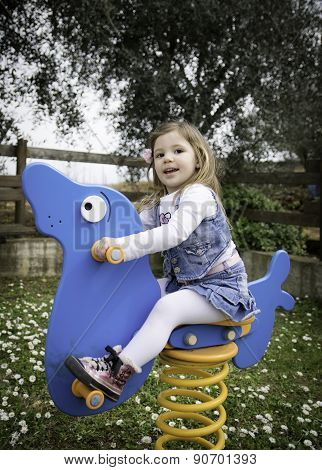 Child Plays On A Blue Spring Seal In A Playground