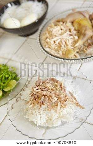 Food preparation for soto, the traditional Indonesian chicken soup. a plate with steamed rice and rice vermicelli and shredded chicken