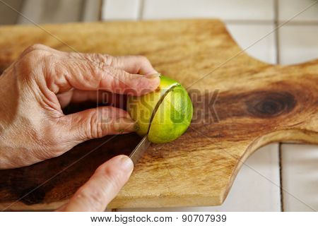 Cutting lime on the wooden cutting board