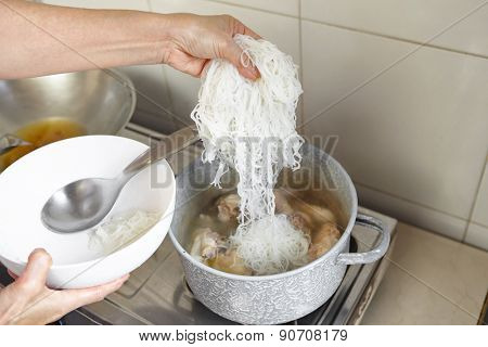 Adding rice noodle to the cooking in pan
