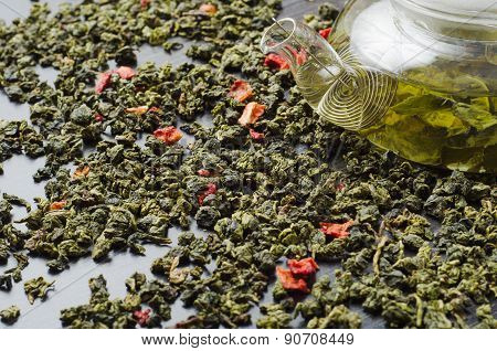 Oolong green tea dried strawberries wooden table with teapot
