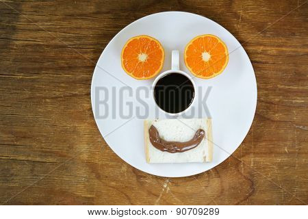breakfast serving funny face on the plate (toast, chocolate spread and orange)