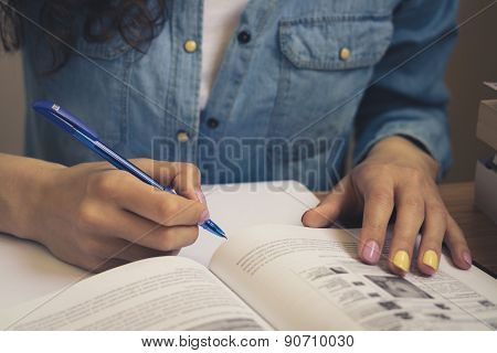 Girl In A Denim Shirt Reading A Textbook And Taking Notes