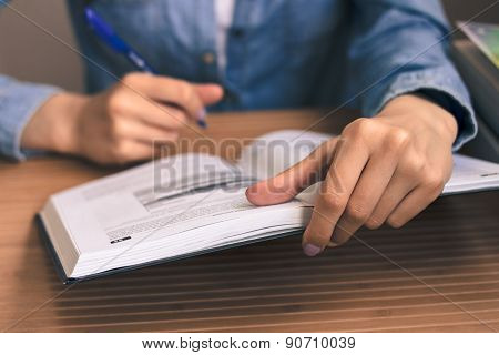 Girl Student In A Blue Denim Shirt Sitting At A Wooden Table And Reading A Textbook
