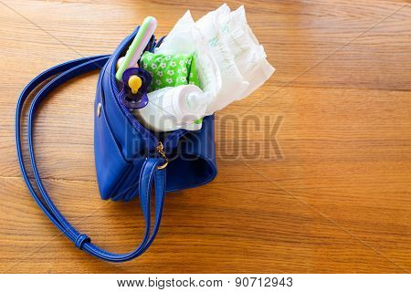 Women's handbag with items to care for the child: the bottle of milk, a pacifier, rattle, clothes