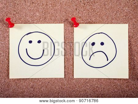 Happy And Sad Faces Pinned To A Noticeboard