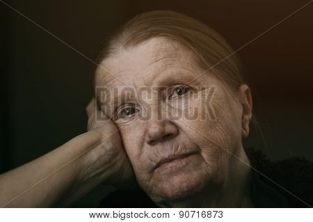 senior woman looking to the camera with sad look shalow DOF
