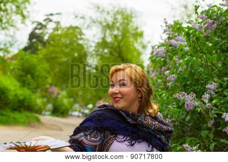Young Woman In Motion On The Background Of Blooming Lilacs, Sparkling Emotions, Flirting, Joy, Laugh