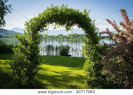 Woven plants forming an arch in garden by the lake
