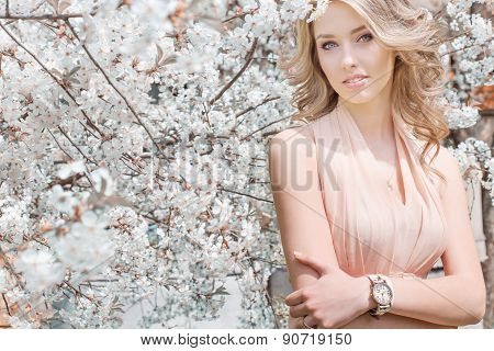 beautiful young tender sweet girl flying in a light dress walking in a lush cherry orchard