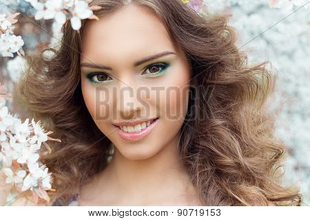 beautiful sexy young tender sweet smiling girl in a flowered garden with beautiful makeup