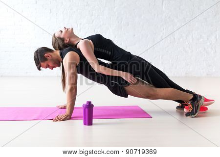 man doing push ups with woman laying on back at gym or home concept fitness sport training teamwork
