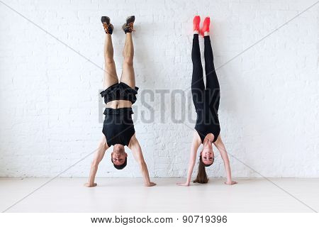 sportsmen woman and man doing a handstand against wall concept balance sport fitness lifestyle peopl