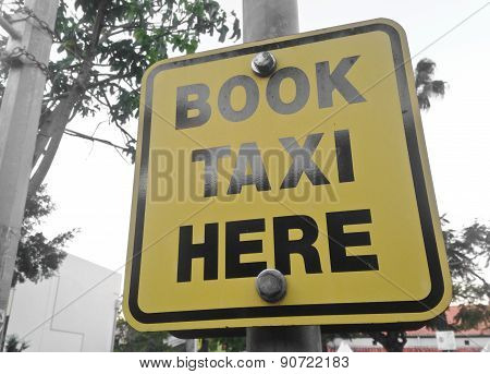 Book Taxi Here Yellow Sign