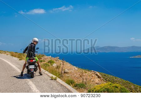 Tourist driving scooter looks back, Greek Island