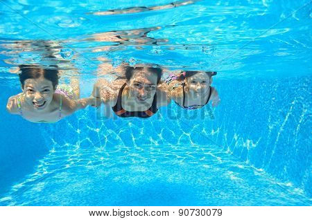 Happy family swim underwater in pool and having fun, mother and children on vacation