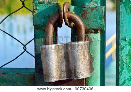 Old Padlock Hanging On A Rusty Steel Gate