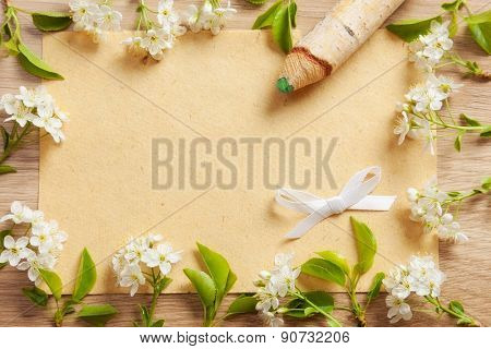 beautiful flowers cherry on branches with a pencil and a sheet of paper texture on the background of wood texture.
