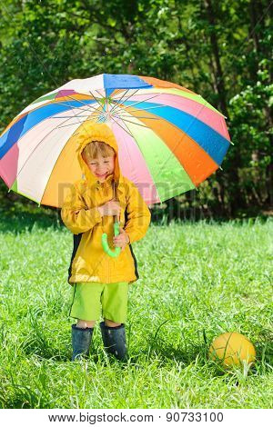 boy with colorful umbrella playing with ball on grass in park