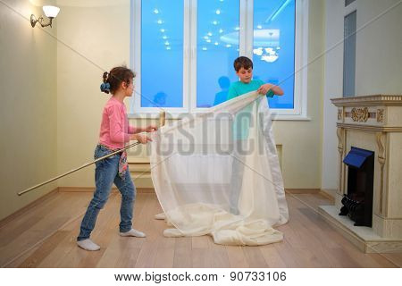 Brother and sister hanging curtains in new apartment in evening