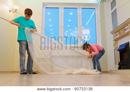 Brother and sister together hanging curtains in new apartment in evening