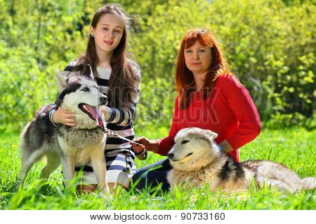 Daughter and mother along with two dogs in park on background of green trees
