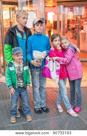 five children stand in front of the mall