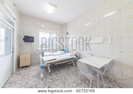 hospital ward with beds tables and tv
