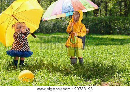 brother and sister with colorful umbrellas in boots and jackets walk in park, ball are in grass