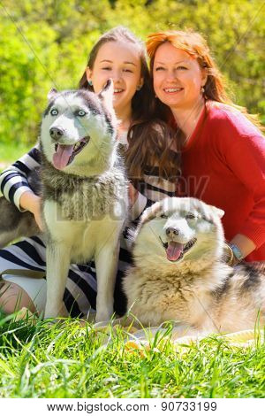 laughing mother and daughter along with two dogs in park on background of green trees, focus on dogs