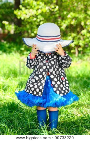 little girl in jacket and boots in park covered her face with hat