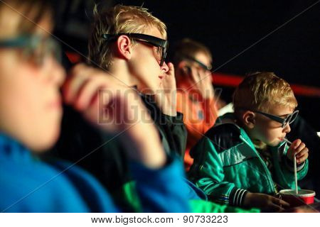 boys watching a movie in 3D glasses at the cinema