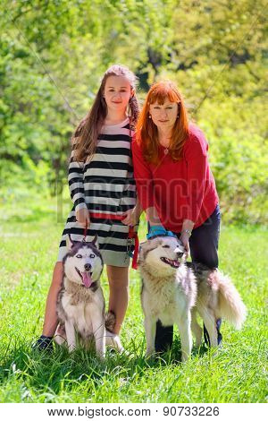 mother and daughter along with two dogs in park on background of green trees, focus on dogs
