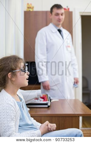 girl checks sight at the reception of an ophthalmologist