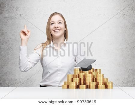Beautiful Blonde Girl Is Thinking About University Education. Graduation Hat Is Laying On The Coins
