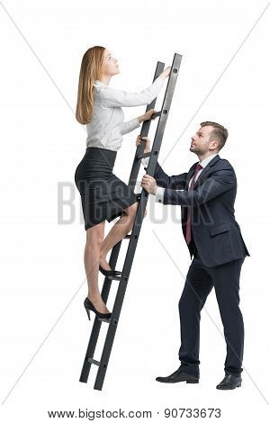 Young Handsome Businessman Is Holding A Ladder For The Lady In A Formal Clothes To Boost Her Ideas.