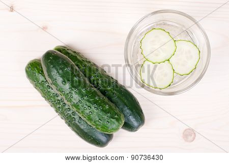 A Glass Of Water With Three Slices Of Fresh Cucumber, Next To Three Cucumber On A Light Table, Top V
