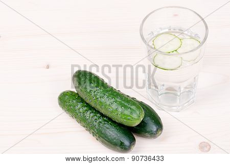 A Glass Of Water With Three Slices Of Fresh Cucumber, Next To Three Cucumber On A Light Table, Side