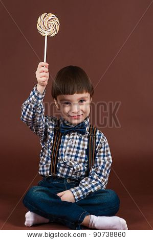 attractive child holding lollipop in hand