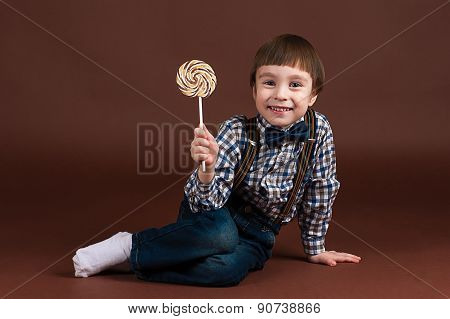 happy child with a lollipop sitting on the floor