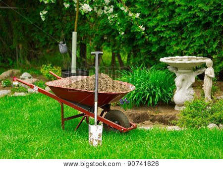 Wheelbarrow Full Of Dirt With Leaning Shovel In Garden
