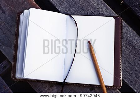 White blank papers in a copybook with a pen on the wooden desk