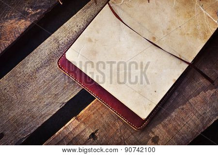 White blank papers in a copybook on the wooden desk