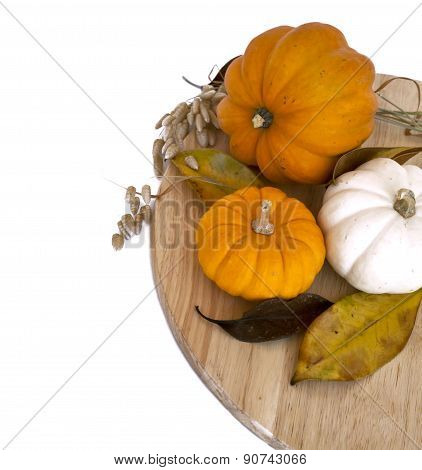Assorted pumpkins and squashes, yellow autumn leaves on round rustic wooden board with copy space wh