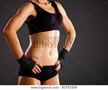 Athletic woman pumping up muscules with dumbbells.