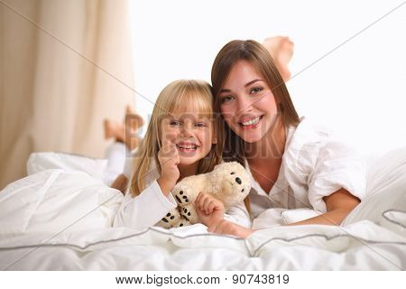 Woman and young girl lying in bed smiling .